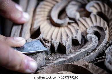 Hands of craftsman carve with a carve tools in the hands.Traditional craftsman carving wood.Thailand