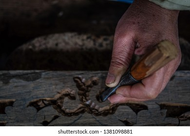 Hands of craftsman carve with carve tools in the hands. Traditional craftsman carving wood.Thailand