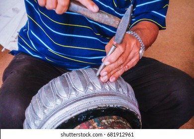 Hands of the craftsman hitting silverware a bas-relief with hammer.