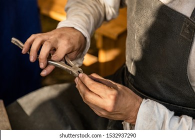 Hands of a craftsman making chain mail, pliers compresses metal rings. Old crafts.  Conducts a master class. Workshop. Dressed in an old outfit.  Demonstration of the craft.