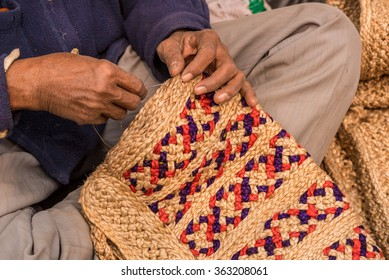Hands of a craftsman weaving handicraft items made of jute
