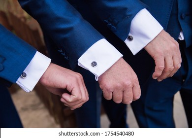 Hands and cuffs of three groomsmen  wearing wedding day suits, close up of cuffs and cufflinks with white shirt beneath blue suit jacket