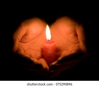 Hands cupped around a burning candle