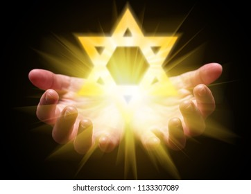 Hands cupped and holding or showing the Star of David. Magen David or Seal of Solomon with bright, glowing, shining light. Concept for Judaism, Jew, Hebrew, Israel, divine or god. Black background