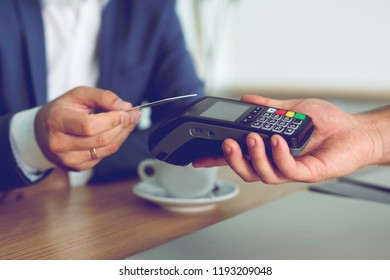 Hands of customer paying restaurant bill using credit card