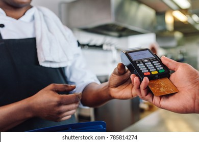 Hands of customer paying restaurant bill using credit card. Customer making payment through credit card at counter in a restaurant.