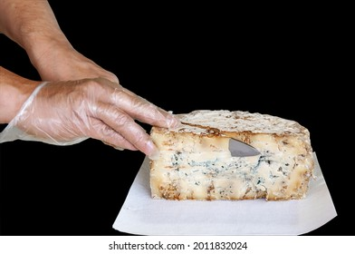 hands cut a large piece of stilton cheese. Isolated on a black background.