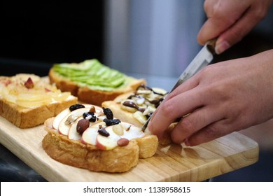 Hands are cuting bread,  cooking toast, wooden tray with toast placed. Healthy toast,  healthy breakfast. Selective focus.