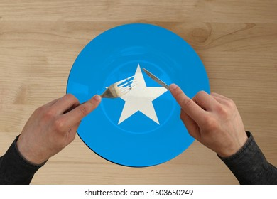 hands with cutlery on a plate with the national flag of Somali, copy space