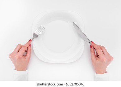 Hands with cutlery over empty plate. A place to place your image.