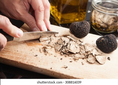 hands cutting Black truffle and knife on wooden background