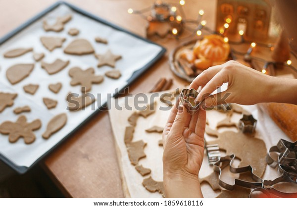 Hands cutting gingerbread dough with festive metal cutters on rustic table with spices, oranges, festive decorations, lights. Person making Christmas gingerbread cookies, holiday advent