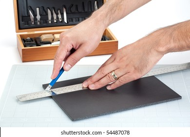 Hands cutting on board with sharp knife