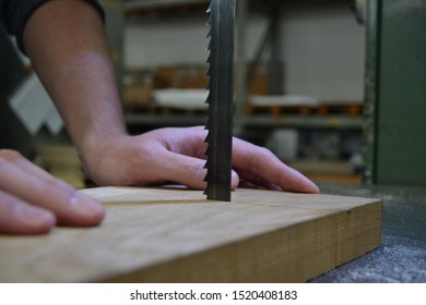 Hands cutting a piece of wood with a bandsaw
