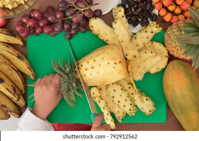 Hands cutting pineapple, cutting fruit for Guatemalan punch.