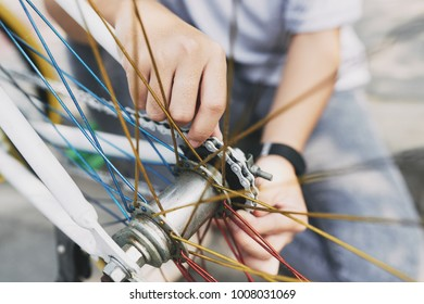 Hands of cyclist removing bicycle wheel