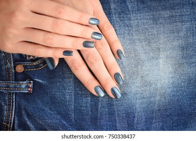 Hands with dark blue manicured nails on jeans textile background