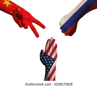 hands decorated in flags of China, United States of America and Russian Federation showing Scissors, paper, stone - symbolizing the difficult political relationship.
