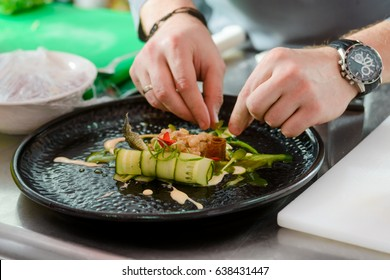 Hands decorating gourmet dish with herbs, close-up. Professional kitchen, restaurant, chef.