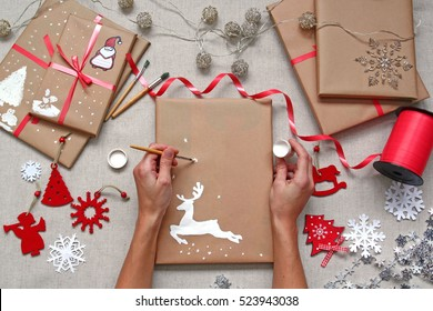 Hands decorating wrapped christmas gifts. Drawing a deer with white paint on brown craft paper of parcel. Top view of present decor accessories.