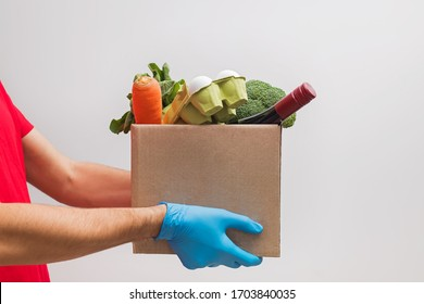 Hands of delivery man wearing protective gloves holding box full of different groceries over the white wall. Online supermarket, delivery during quarantine concept