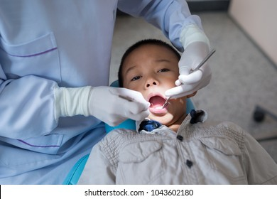 Hands of dentist holding a dental tool. Checking the teeth to the boy lying in the dental chair in a hospital.