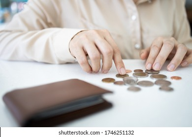Hands of desperate asian woman is counting her last remaining coins from her wallet on white table,poverty and absence of money,unemployed,financial problems,economic crisis from Covid-19 pandemic