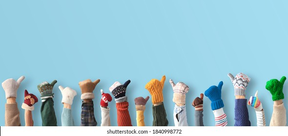 Hands up up in the different mittens. Winter concept.