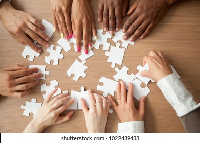 Hands of diverse people assembling jigsaw puzzle, african and caucasian team put pieces together searching for right match, help support in teamwork to find common solution concept, top close up view