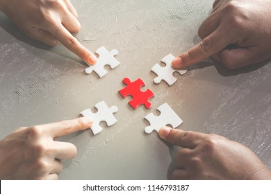 Hands of diverse people assembling jigsaw puzzle,  help support in teamwork to find common solution concept, top close up view