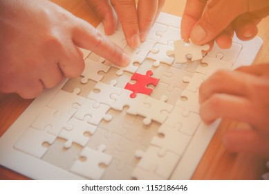 Hands of diverse people assembling jigsaw puzzle, team put pieces together searching for right match, help support in teamwork to find common solution concept