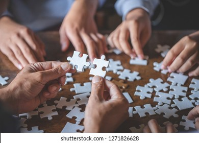 Hands of diverse people assembling jigsaw puzzle, team put pieces together searching for right match, help support in teamwork to find common solution concept, top close up view