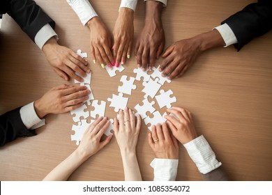 Hands of diverse people connecting puzzle together on office desk, multi-ethnic team engaging in finding best business solutions for successful teamwork, teambuilding unity concept, top close up view