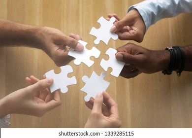 Hands of diverse team members assembling jigsaw puzzle on desk close up, African American and Caucasian colleagues finding solution, working on project together, help and support in teamwork concept