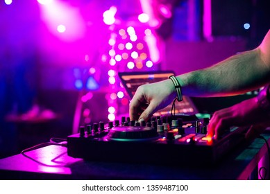 hands DJ mixing and playing music on a professional controller mixer Board in a nightclub at a party