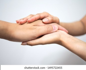 Hands of doctor holding the hand of a patient for the consolation
