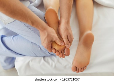 Hands of doctor masseur making manual massage of feet for lying woman in wellness clinic, top view. Professional chiropractor during work concept