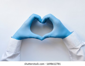 Hands of a doctor or nurse in medical gloves depict a heart on a white background, caring doctor and medicine concept