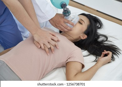Hands of doctors giving cardiac massage and resuscitation to a female patient in the bedroom, Concept of Emergency Medical Team