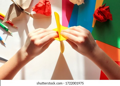 Children's hands doing origami crane from yellow paper on white background with various school supplies. Step-by-step tutorial of origami. Step 6. Concept of children's creativity, back to school.
