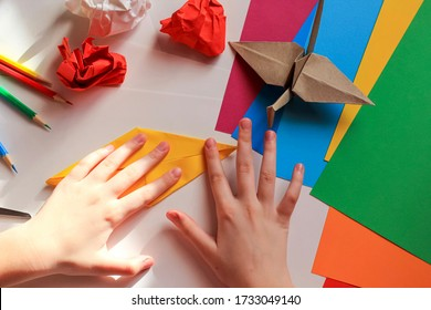Children's hands doing origami crane from yellow paper on white background with various school supplies. Step-by-step tutorial of origami. Step 11. Concept of children's creativity, back to school.
