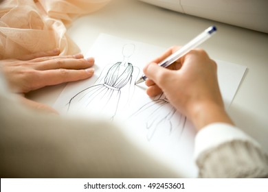 Hands drawing a black ink clothing design sketch, view over the shoulder, closeup, close-up