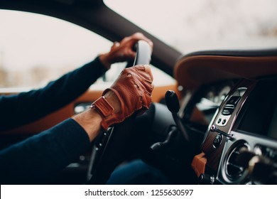 The hands of the driver in leather gloves, driving a moving car.