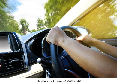 Hands of a driver on steering wheel of a car and empty asphalt road.