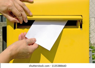 hands dropping blank envelope into a post box
