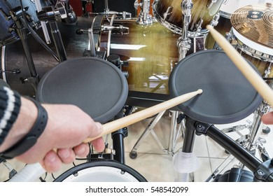 Hands drummer drumsticks knock on the black electric drum, close-up in the first person