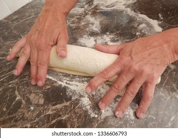 Hands dust, roll, pat, knead, and shape a homemade bread baguette.
