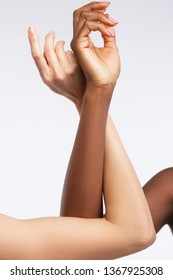 Hands and elbows. Women with different skin touching their hands and elbows posing for diversity campaign