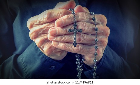 Hands of an elder woman holding a rosary while praying,Christian daily devotional of a worshiper, relationship with God the Creator and Savior