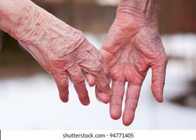 Hands of an elderly couple, close-up.